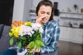 mladá žena s alergií, kýchání a drží kytici květin