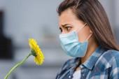 boční pohled na mladou ženu s alergií zdravotní masku a při pohledu na květinu