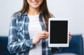 vágott mosolygó lány gazdaság digitális tabletta-val üres képernyő szemcsésedik