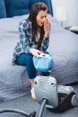 pohled z úhlu vysoké dívky s alergii drží kontejneru z odsavače prachu s prachem a kýchání v ložnici