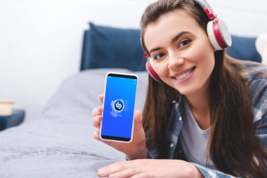 attractive girl in headphones holding smartphone with shazam app and smiling at camera while lying on bed
