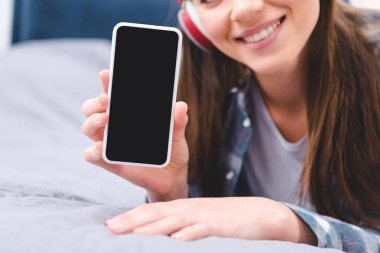 cropped shot of smiling young woman in headphones holding smartphone with blank screen while lying on bed
