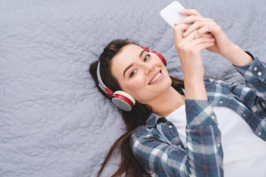 happy young woman in headphones using smartphone on bed and smiling at camera
