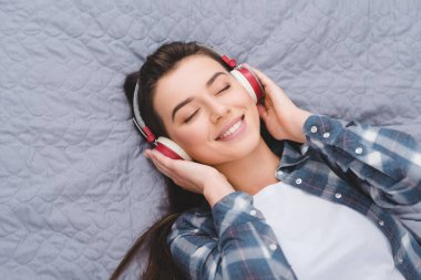 beautiful smiling girl in headphones lying on bed