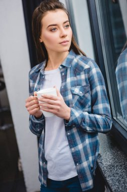 beautiful pensive young woman holding cup and looking at window