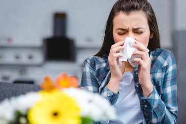 young woman with allergy holding facial tissue and sneezing, flowers on foreground