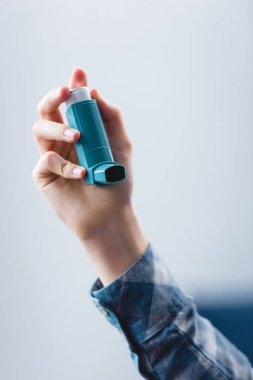 close-up partial view of young woman holding asthma inhaler