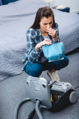 high angle view of young woman with allergy sneezing while holding container from vacuum cleaner with dust
