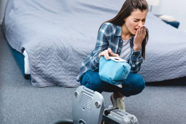 high angle view of girl with allergy sneezing while holding container from vacuum cleaner with dust