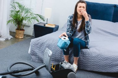 high angle view of woman with allergy holding container from vacuum cleaner with dust and sneezing in bedroom
