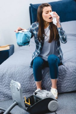 girl with allergy holding container from vacuum cleaner with dust and sneezing in bedroom