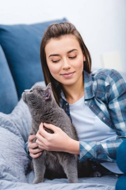 beautiful smiling girl lying on bed with adorable british shorthair cat
