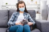 dívka v lékařské masky drží kočku a trpící alergií na doma