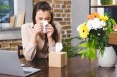 Fotografie mladá podnikatelka smrkání a trpící alergií na pracovišti