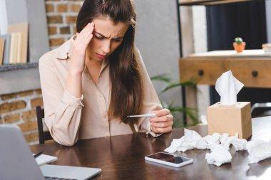 Termometre tutarak ve office sıcaklık kontrol hasta genç iş kadını