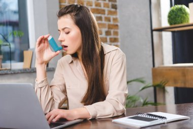 young businesswoman with asthma using inhaler in office