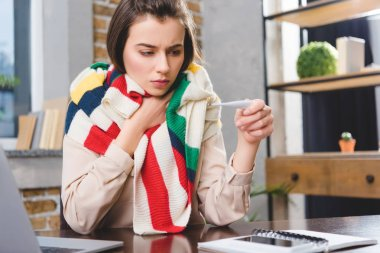 Sick young businesswoman in scarf holding thermometer and checking temperature at workplace stock vector