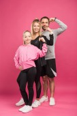 Photo strong athletic family in sportswear showing muscular biceps, isolated on pink