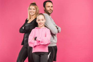 athletic family posing in sportswear with crossed arms, isolated on pink