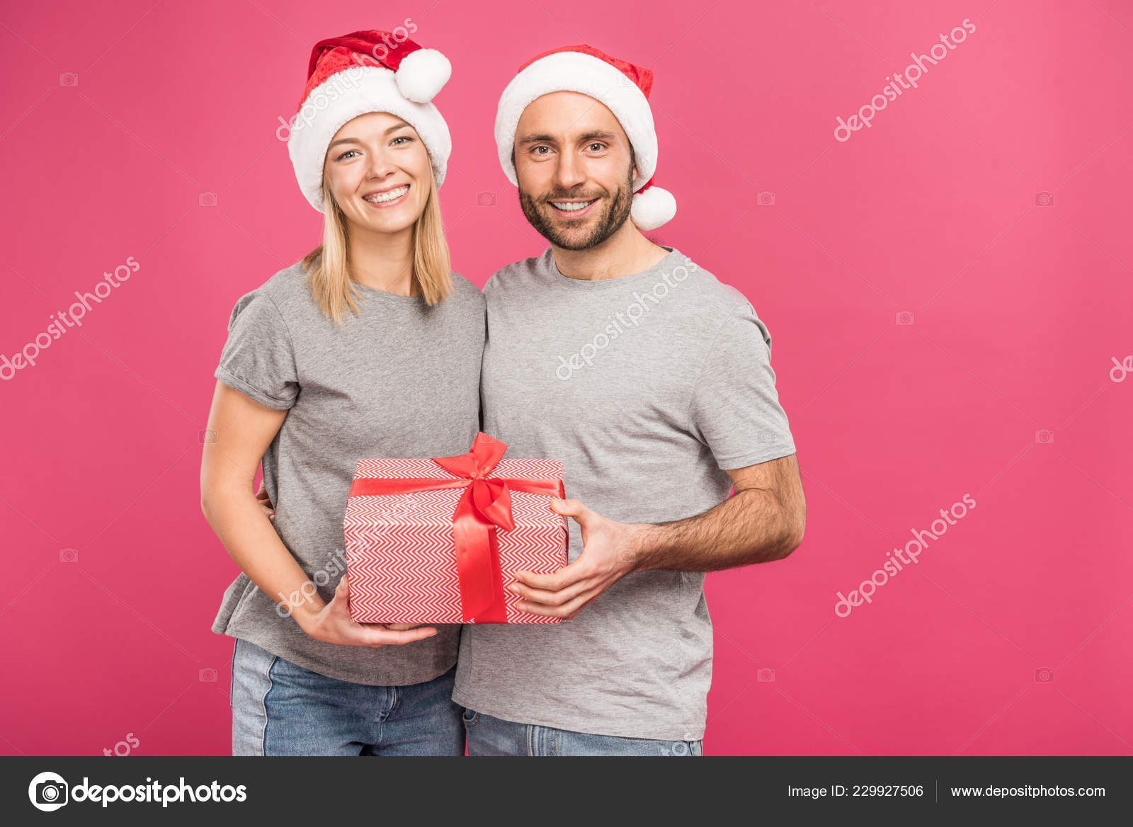 f3d2e63ad6976 Smiling Couple Santa Hats Hugging Holding Christmas Gift Box Isolated —  Stock Photo