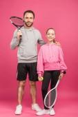 pohledný otec a dcera drží tenisové rakety a míček, izolované na růžové