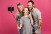 usmívající se rodinné pořizování selfie na smartphone zároveň dcera zobrazeno symbol míru, izolované na růžové