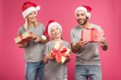 Fényképek boldog családi gazdaság karácsonyi santa kalap bemutatja elszigetelt a rózsaszín