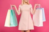 a boldog nő, bevásárló táskák, elszigetelt rózsaszín levágott megtekintése