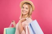 zákazník blondýnka v slaměný klobouk drží nákupní tašky, izolované na růžové