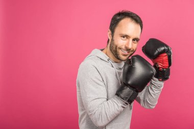smiling male boxer training in box gloves, isolated on pink