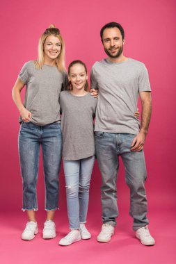 beautiful parents hugging with happy daughter, isolated on pink