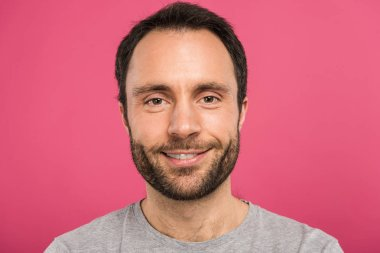 portrait of handsome smiling man looking at camera, isolated on pink