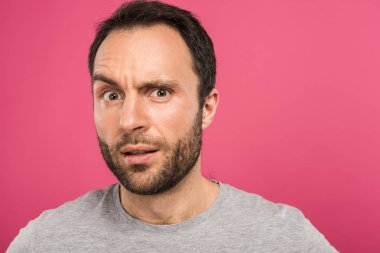portrait of confused man looking at camera, isolated on pink
