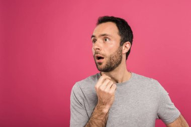 portrait of shocked man looking aside, isolated on pink