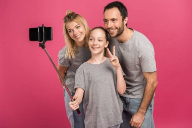 smiling family taking selfie on smartphone while daughter showing peace symbol, isolated on pink