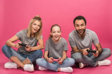 Excited family playing video game with joysticks, isolated on pink stock vector