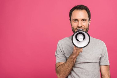 happy handsome man speaking with megaphone, isolated on pink