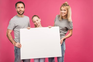 Smiling family posing with blank card, isolated on pink stock vector