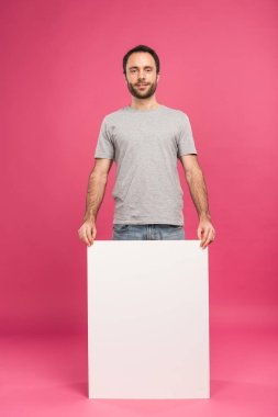 Handsome man posing with empty board, isolated on pink stock vector