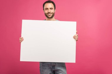 Cheerful man posing with empty board, isolated on pink stock vector