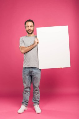 Handsome man posing with blank board, isolated on pink stock vector