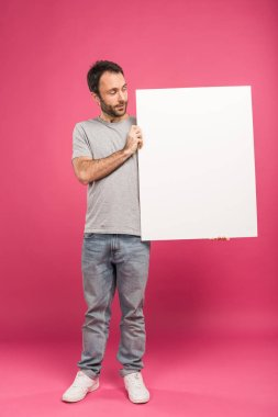 Handsome adult man holding blank board, isolated on pink stock vector