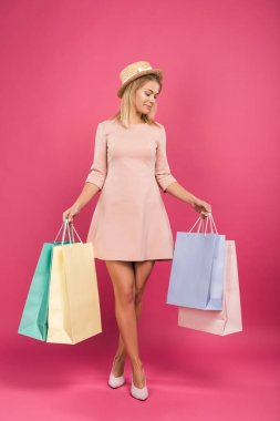 attractive woman in dress holding shopping bags, isolated on pink