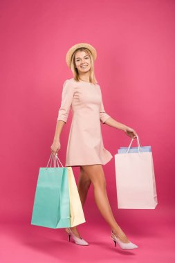 pretty smiling woman with shopping bags, isolated on pink