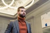cílené pohledný muž v oblasti formální oblečení, pózování a hledat dál