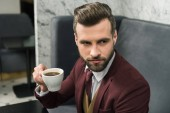bearded handsome businessman in formal wear sitting at table and drinking coffee in restaurant