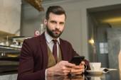 vážně hezký podnikatel v oblasti formální oblečení sedí u stolu s kávou a pomocí smartphone v restauraci