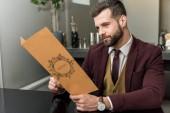 jóképű üzletember a hivatalos viselet ül az étteremben és a gazdaság menü