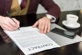 abgeschnittene Ansicht von Geschäftsmann in formeller Kleidung am Tisch sitzend und Vertrag unterzeichnend