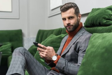 handsome man in formal wear sitting on green sofa, looking at camera and using smartphone